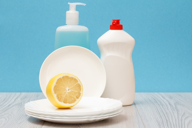 Bottiglie di plastica di detersivo per piatti, detergente per vetri e piastrelle, piatti puliti e limone su sfondo blu. concetto di lavaggio e pulizia.