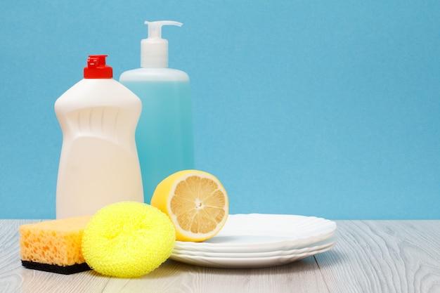 Bottiglie di plastica di detersivo per piatti, detergente per vetri e piastrelle, piatti puliti, limone e spugne su sfondo blu. concetto di lavaggio e pulizia.