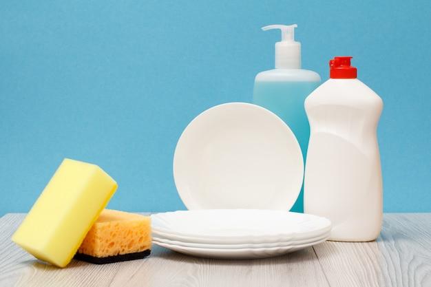 Bottiglie di plastica di detersivo per piatti, detergente per vetri e piastrelle, piatti puliti e spugne su sfondo blu. concetto di lavaggio e pulizia.