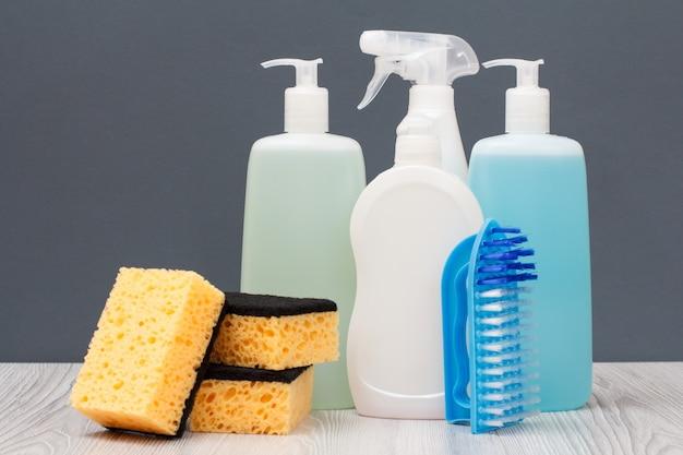 Bottiglie di plastica di detersivo per piatti, detergente per vetri e piastrelle, detergente per forni a microonde e fornelli, spazzola e spugne su sfondo grigio. concetto di lavaggio e pulizia.