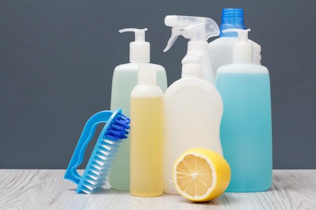 Bottiglie di plastica di detersivo per piatti, detergente per vetri e piastrelle, detergente per forni a microonde e stufe, pennello e limone su sfondo grigio. concetto di lavaggio e pulizia.