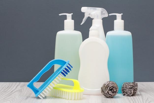 Bottiglie di plastica di detersivo per piatti, detergente per vetri e piastrelle, detergente per forni a microonde e stufe, spazzole e spugne metalliche su sfondo grigio. concetto di lavaggio e pulizia.