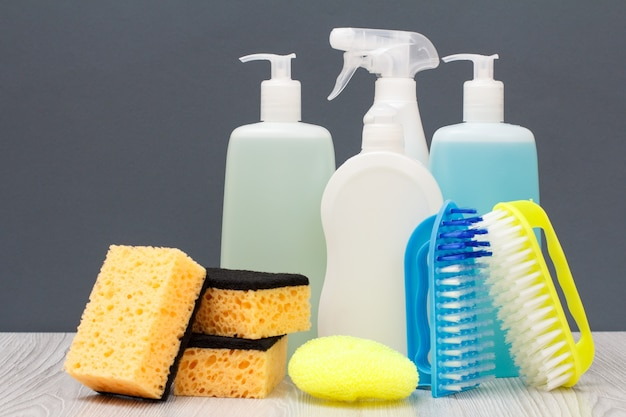 Bottiglie di plastica di detersivo per piatti, detergente per vetri e piastrelle, detergente per forni a microonde e stufe, spazzole e spugne su sfondo grigio. concetto di lavaggio e pulizia.