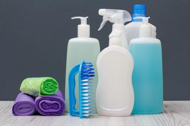Bottiglie di plastica di detersivo per piatti, detergente per vetri e piastrelle, detergente per forni a microonde e stufe, sacchetti della spazzatura e spazzola su sfondo grigio. concetto di lavaggio e pulizia.