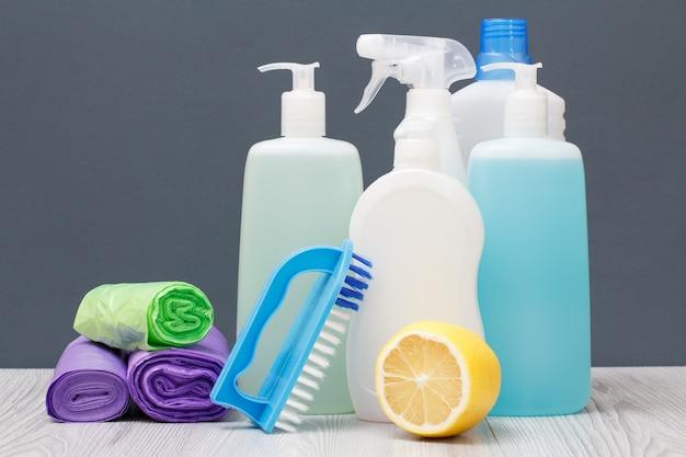 Bottiglie di plastica di detersivo per piatti, detergente per vetri e piastrelle, detergente per forni a microonde e stufe, sacchetti della spazzatura, spazzola e limone su sfondo grigio. concetto di lavaggio e pulizia.