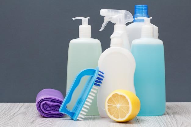 Bottiglie di plastica di detersivo per piatti, detergente per vetri e piastrelle, detergente per forni a microonde e stufe, sacchetti della spazzatura, pennello e limone su sfondo grigio. concetto di lavaggio e pulizia.