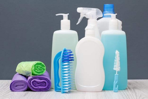 Bottiglie di plastica di detersivo per piatti, detergente per vetri e piastrelle, detergente per forni a microonde e stufe, sacchetti della spazzatura e spazzole su sfondo grigio. concetto di lavaggio e pulizia.