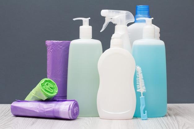 Bottiglie di plastica di detersivo per piatti, detergente per vetri e piastrelle, detergente per forni a microonde e stufe e sacchetti della spazzatura su sfondo grigio. concetto di lavaggio e pulizia.