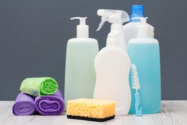 Bottiglie di plastica di detersivo per piatti, detergente per vetri e piastrelle, detergente per forni a microonde e stufe, sacchetti della spazzatura e spugna su sfondo grigio. concetto di lavaggio e pulizia.