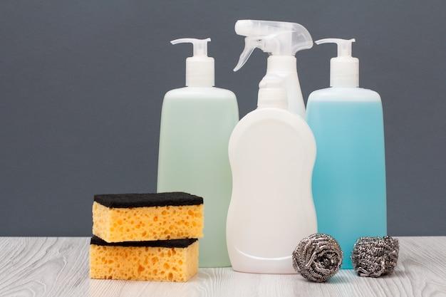 Bottiglie di plastica di detersivo per piatti, detergente per vetri e piastrelle, detergente per forni a microonde e stufe, spugne su sfondo grigio. concetto di lavaggio e pulizia.
