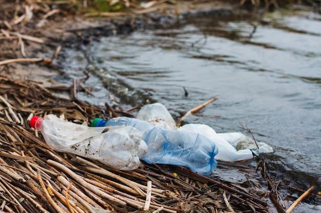 Bottiglie di plastica sulla riva del fiume, concetto per il giorno della protezione degli oceani. immondizia di plastica non degradabile sulla costa.