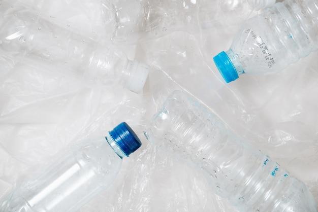 Pila di bottiglie di plastica da riciclare su sfondo bianco