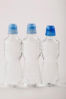 Bottiglie di plastica di acqua con vista frontale tappi blu Foto Premium