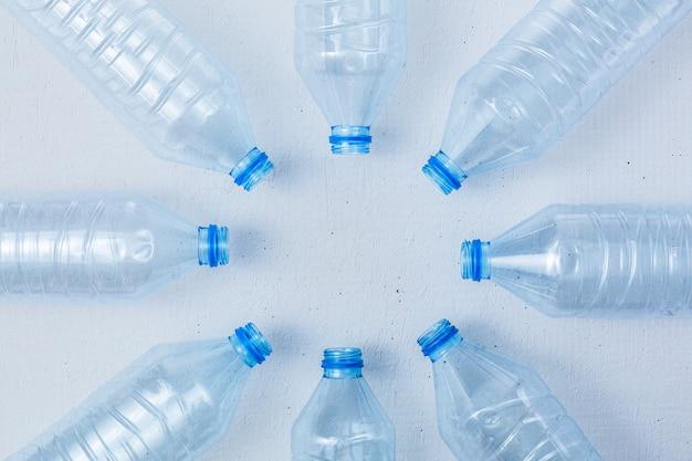Bottiglie di plastica su sfondo bianco come simbolo di catastrofi ecologiche