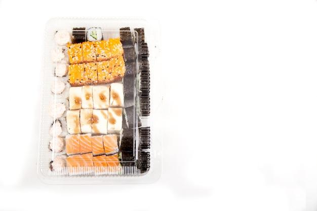 Scatola di plastica con un set di vari sushi, rotoli su uno sfondo bianco. consegna a domicilio di generi alimentari. copia spaes.