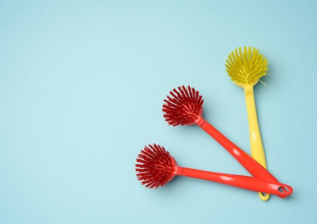 Spazzole in plastica con manici per la pulizia su sfondo blu, primi piani