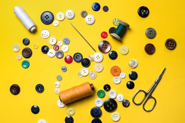 Bottoni in plastica e rocchetti di filo con aghi da cucito