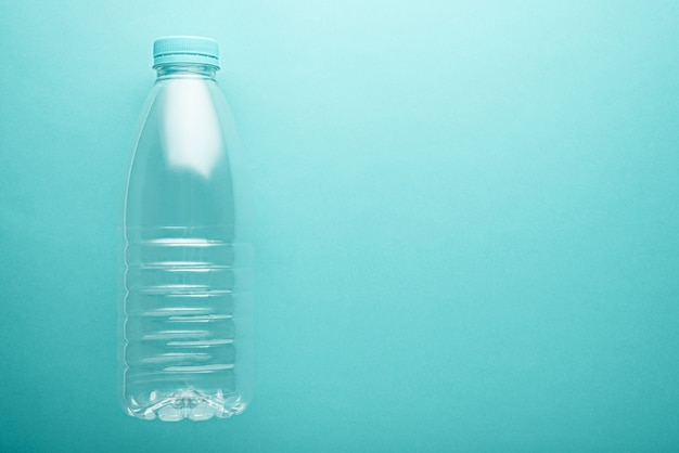 Bottiglia di acqua pulita in plastica con coperchio blu con spazio di copia su sfondo neo menta. concetto di inquinamento ambientale