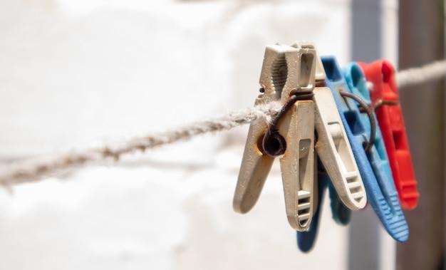 Mollette di plastica appese in fila sulla corda. corda all'aperto, su uno sfondo sfocato in un giardino soleggiato. stendibiancheria per strada. mollette.