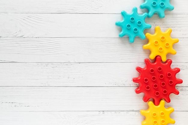 Ruote dentate di plastica del costruttore su fondo di legno bianco. giocattoli popolari. copyspace