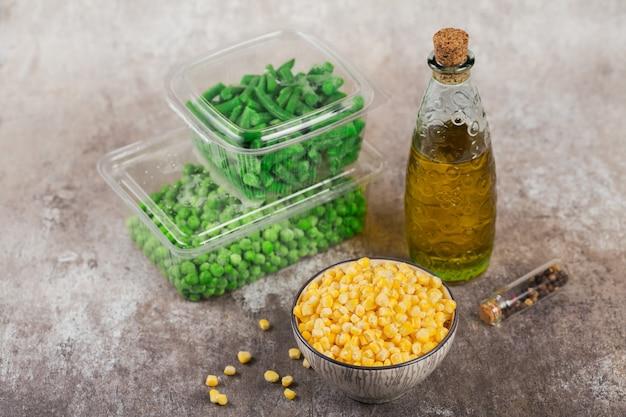 Contenitore di plastica con diverse verdure surgelate organiche sul tavolo. piselli, mais e fagiolini tagliati in scatola