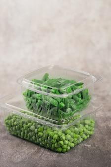 Contenitore di plastica con diverse verdure surgelate organiche su un tavolo