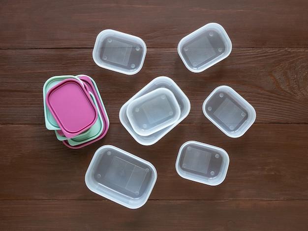 Contenitori in plastica per il trasporto e lo stoccaggio di prodotti alimentari disposti su un tavolo di legno