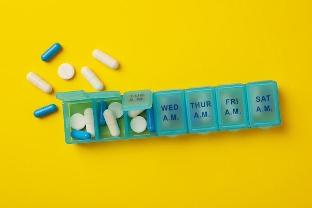 Contenitori di plastica con pillole su colore giallo