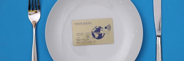 La carta di credito in plastica è sul piatto bianco. offerte bancarie per il concetto di business