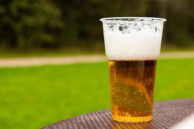 Bicchiere di birra in plastica sul tavolo. messa a fuoco selettiva.