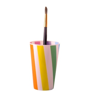 Bicchiere di plastica con un pennello per dipingere il taglio isolato