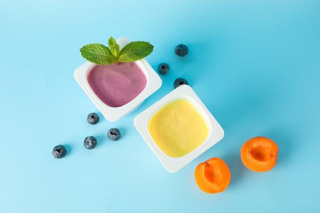 Bicchieri di plastica con yogurt e frutta su sfondo colorato,