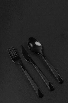 Coltello, cucchiaio e forchetta neri monouso in plastica su sfondo scuro dark