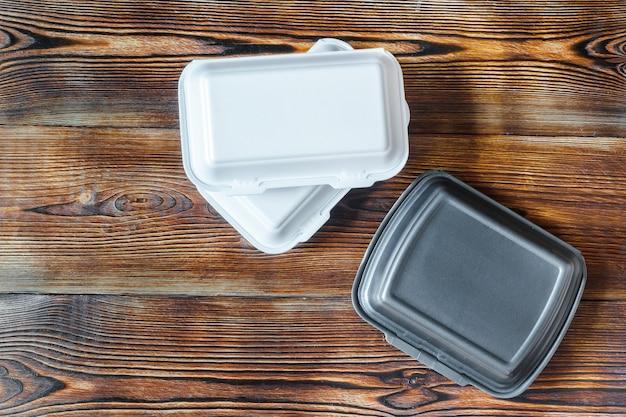 Contenitori per alimenti usa e getta in plastica su ordine di fondo in legno. servizio di consegna cibo dal ristorante