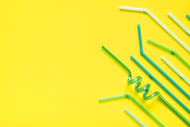 Tubi di plastica per bevande su sfondo giallo con spazio per il testo.