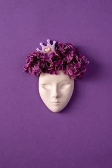 Maschera facciale in plastica decorata con fiori lilla e corona in miniatura su sfondo viola