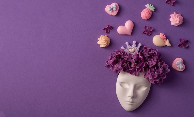 Maschera facciale in plastica decorata con fiori lilla e miniature di corone e dolci su sfondo viola