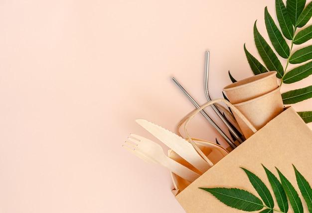 Set senza plastica con bambù, posate di carta e cannucce di metallo su sfondo rosa.