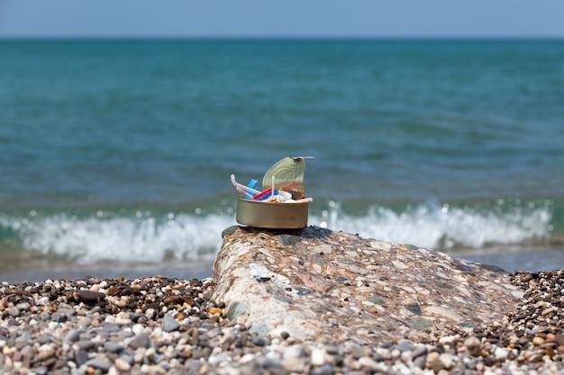 Rifiuti di plastica raccolti in riva al mare in barattoli di latta consumo eccessivo di imballaggi usa e getta