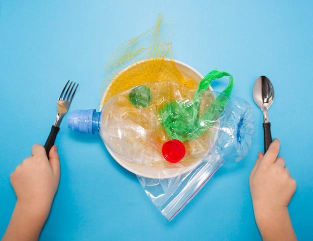 Immondizia di plastica su un piatto, le mani del bambino che tengono una forchetta e un cucchiaio da mangiare. concetto inquinamento ambientale, inquinamento plastico.