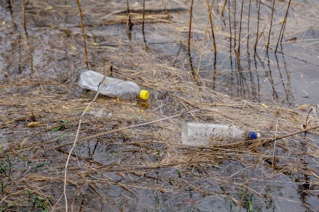 Bottiglie di plastica e vetro nel fiume
