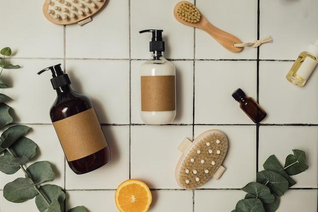Bottiglie di plastica e vetro marrone con cosmetici biologici ecologici, eucalipto verde e arance tagliate dall'alto. concetto di minimalismo di bellezza. ingredienti cosmetici naturali per la cura della pelle.