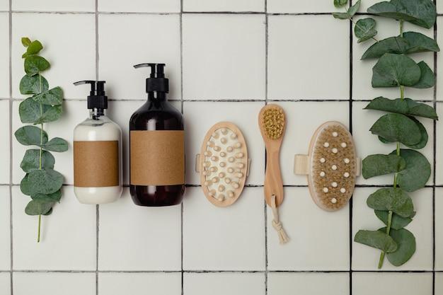 Bottiglie di plastica e vetro marrone con cosmetici biologici ecologici, eucalipto verde e dall'alto. concetto di minimalismo di bellezza. ingredienti cosmetici naturali per la cura della pelle.