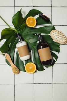 Bottiglie di plastica e vetro marrone con cosmetici biologici ecologici, foglia di monstera verde e arance tagliate dall'alto. concetto di minimalismo di bellezza. ingredienti cosmetici naturali per la cura della pelle.