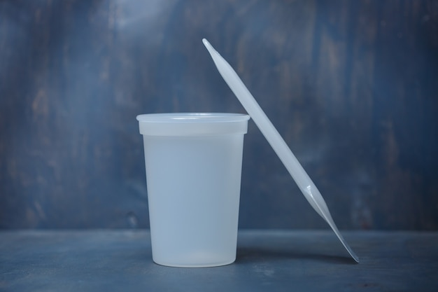 Bicchiere di plastica per mescolare la panna su fondo grigio