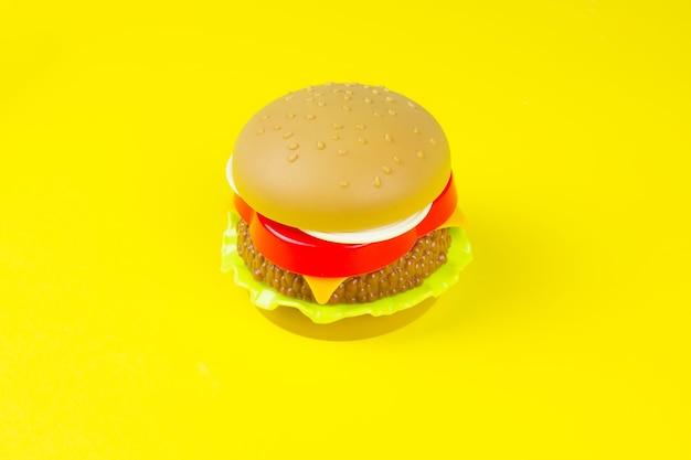 Hamburger di plastica su sfondo giallo. giocattolo dell'hamburger del primo piano su fondo giallo.