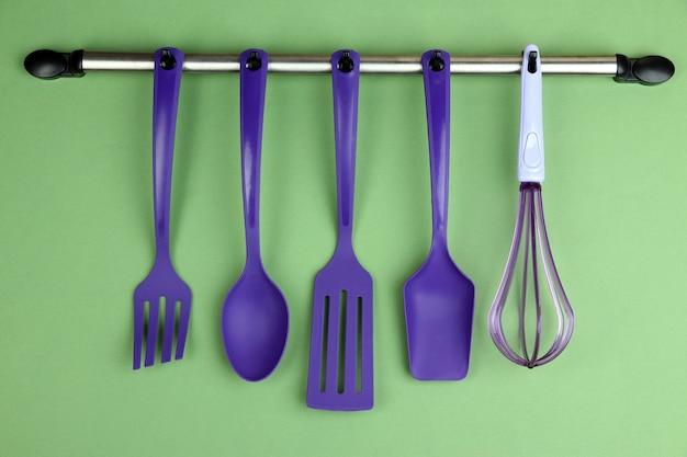 Utensili da cucina in plastica su ganci d'argento su sfondo verde