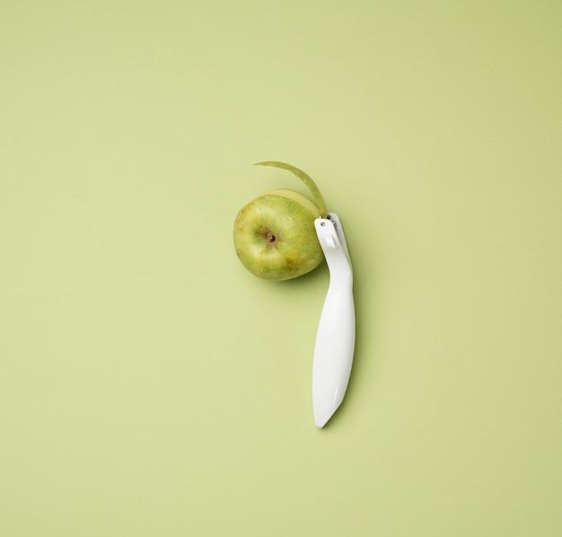 Coltello in plastica per pelare verdura, frutta e una mela verde su sfondo verde, vista dall'alto