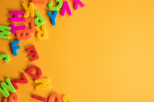 Le lettere di plastica sono sparse sul tavolo arancione