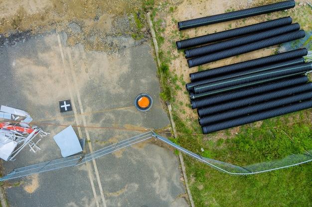 Tubi neri principali in plastica su un mucchio di tubi in polietilene per un sistema di approvvigionamento idrico per la posa delle comunicazioni urbane di casa